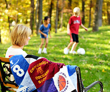 mom on bench watching kids play soccer