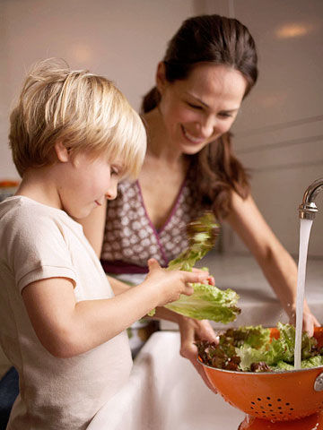 Mother and son washing lettuce at the kitchen sink