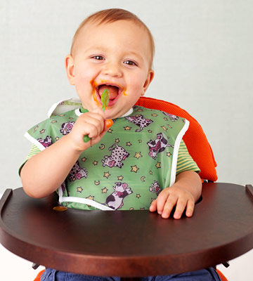 baby in high chair licking a spoon