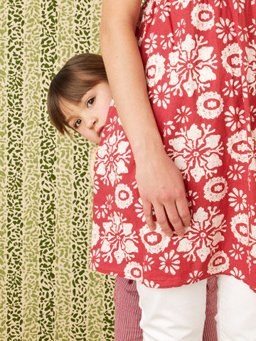 Young girl hiding behind her mom