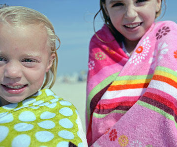 girls wrapped in towels on the beach