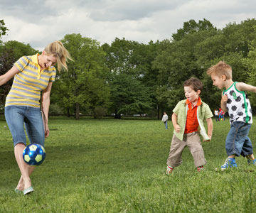 Woman playing soccer with two boys