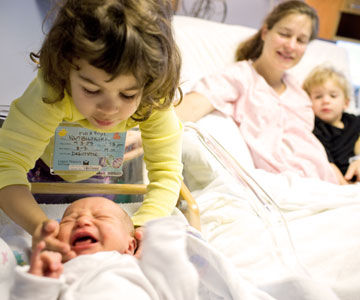 family loooking at new baby in the hospital