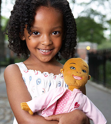 Child holding Kimmie Care doll