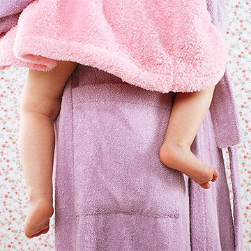 mother holding toddler in bathrobe