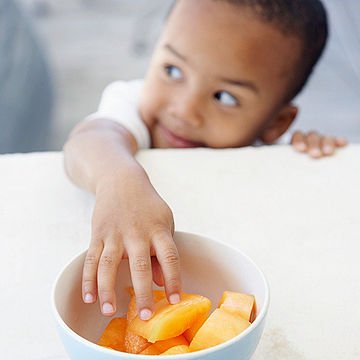 child reaching for cantaloupe