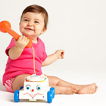 baby playing with old style telephone