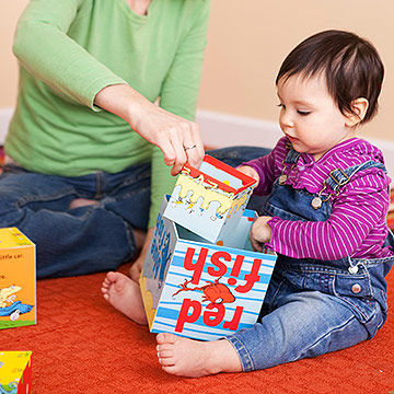 helping toddler with stacking toy