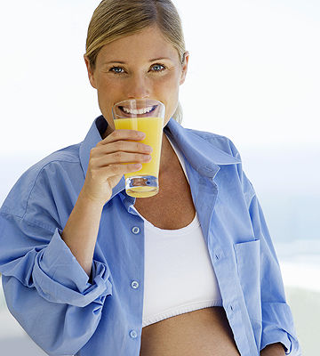 pregnant woman drinking orange juice