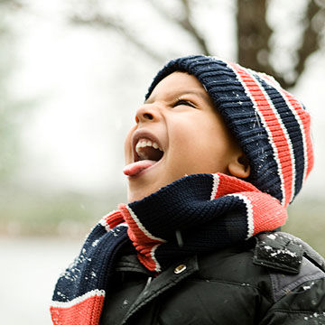 child catching snow in mouth