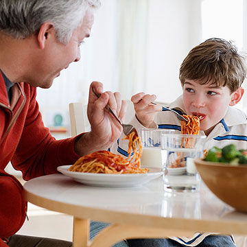 father and son talking at the dinner table