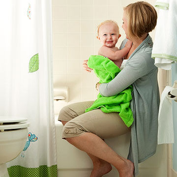 mother taking child out of bath