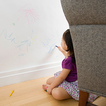 child coloring on wall with crayon