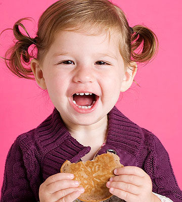 child eating nut pancakes