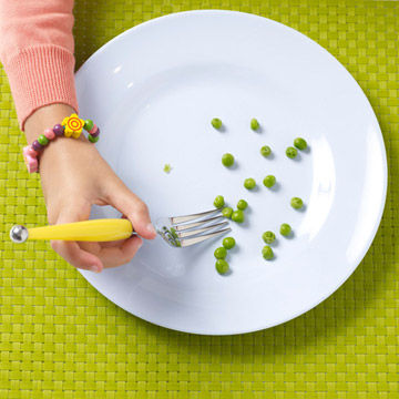 Child picking at peas on plate