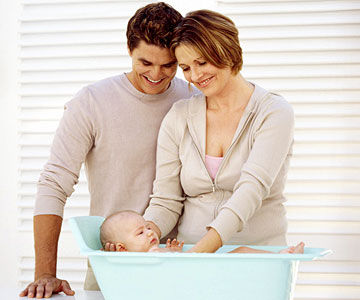 Wavy haired dad and mom washing baby in blue tub