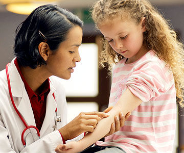 doctor inspecting child's arm