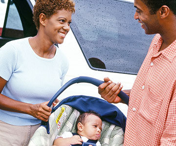 mom and dad with baby in car seat