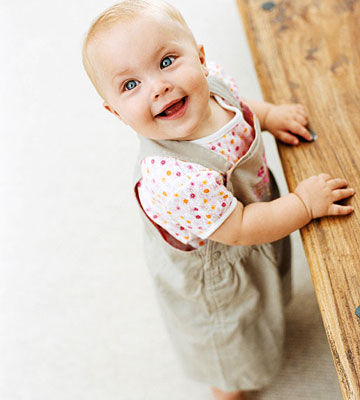 baby holding self up with coffee table