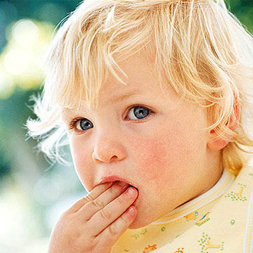 toddler putting food in mouth