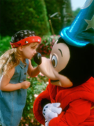 Preschool girl kissing Mickey Mouse