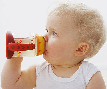 baby holding sippy cup