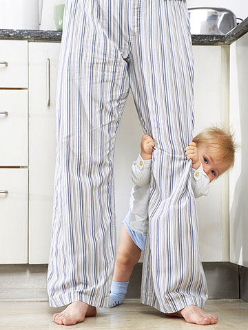 baby standing up holding parents leg