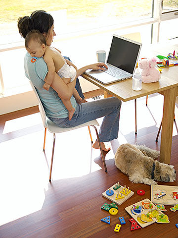 mother holding baby on computer