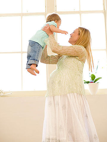 woman holding up baby