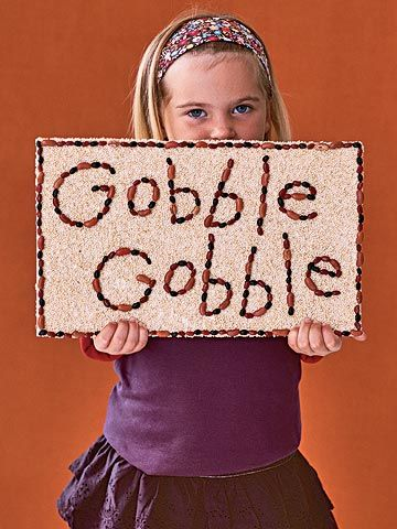 girl holding her Thanksgiving craft
