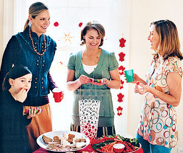 women standing around small table eating snacks
