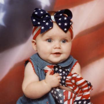 Little Girl With Big Flag Bow On Head In Jean Dress