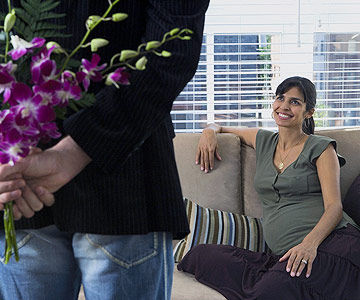 man surprising pregnant woman with flowers