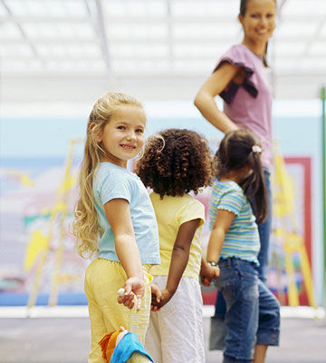 girls holing hands in line with teacher. 8 Ways to Solve Potty Training s Biggest Challenges