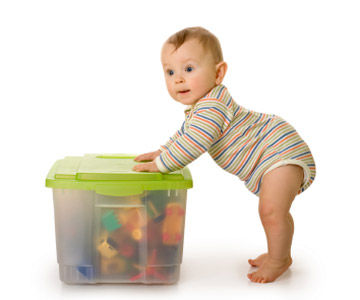 baby leaning on bin of toys