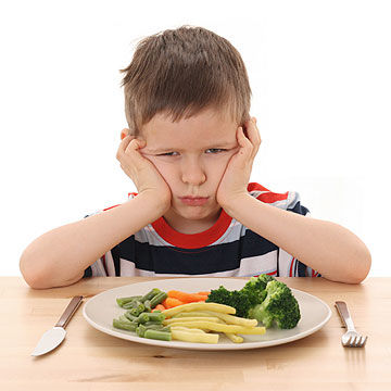 angry boy with plate of vegetables