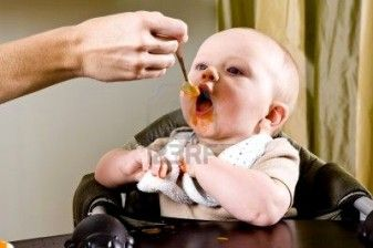 Baby eating solid food from a spoon