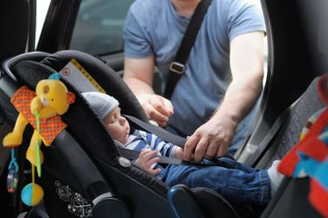 Baby Being Put in Car Seat