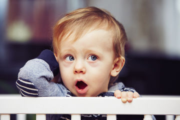 yawning toddler boy in crib