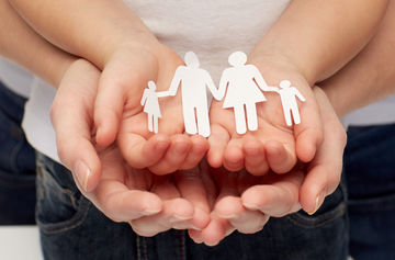 Hands holding paper cut off of family