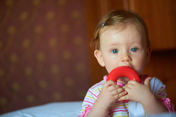 Baby with Blue Eyes and Teething Ring