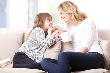 Mom and young daughter talking on couch
