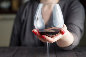 Woman holding a glass of wine at wine tasting