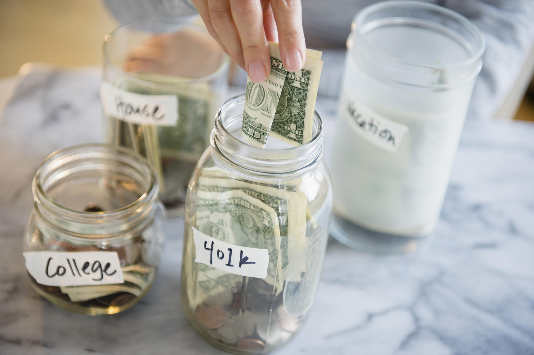 Woman saving money for college and retirement in jars