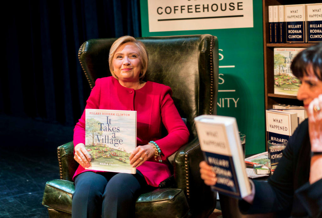 """Former Secretary of State Hillary Clinton holds her children's book """"It takes a Village"""""""
