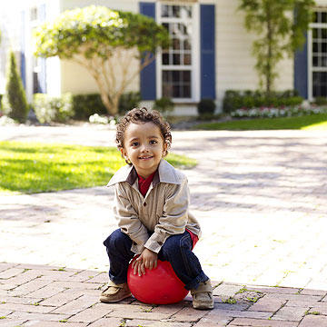 child sitting outside on ball