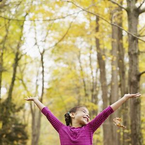 Girl with arms above her head in fall