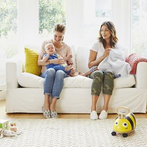 Two Moms Sitting on Couch with babies