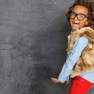Young Girl Jumping Red Pants Fur Jacket and Glasses