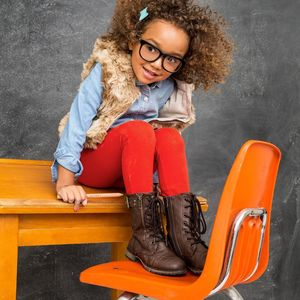 Young Girl Sits on School Desk and Chair